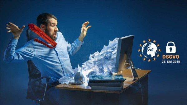 Konzeptbild: Gestresster Geschäftsmann überfordert von Papierkram, der aus dem Computerbildschirm strömt.